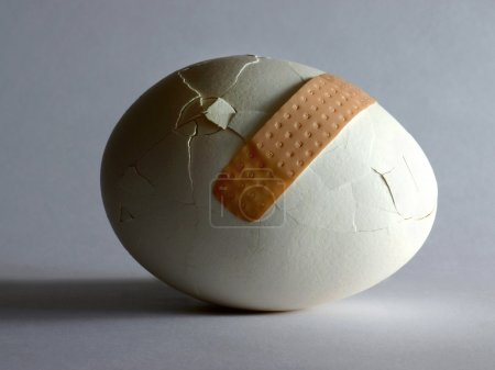 Broken egg with sticking plaster